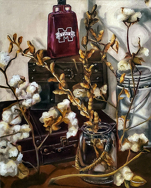 Still life arrangement with dried cotton plants in glass jars, leather suitcases, and maroon cowbell.