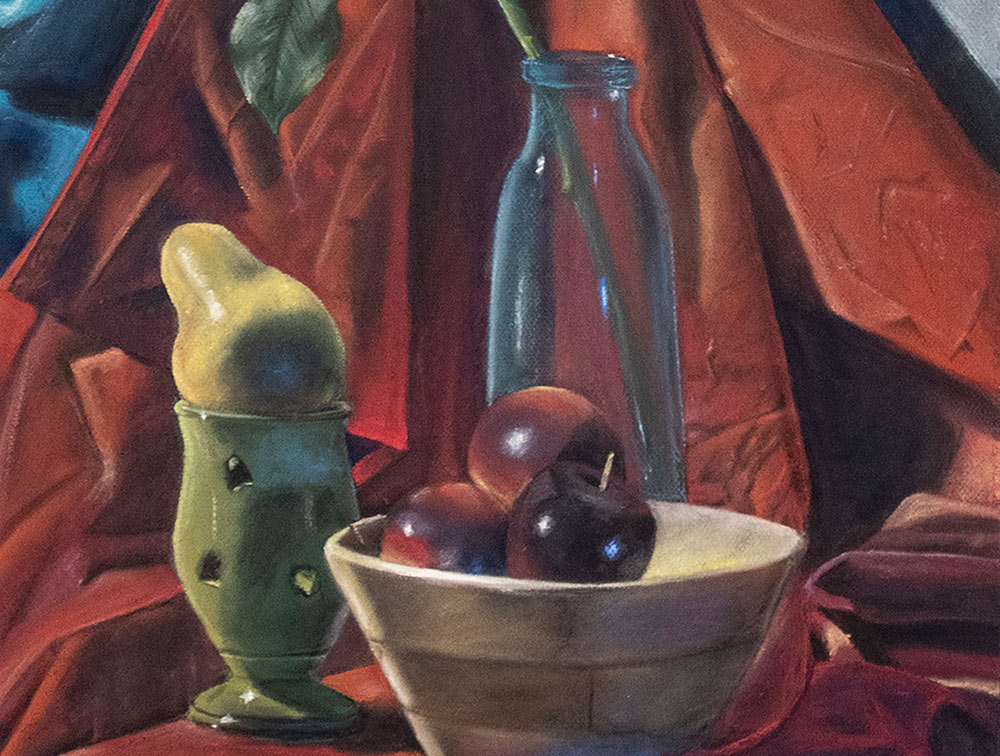"""Blue Glass,"" a drawing by MSU sophomore art/graphic design major Emily R. Harms of Madison, is a colorful still life - shows wooden bowl with 3 red apples in front, green glass cup behind on left with a pear resting on top, blue see-through milk-type glass container at center back with a single stem with leaves coming out of it; burgundy drapery is the backdrop; touch of blue seen at top left corner"