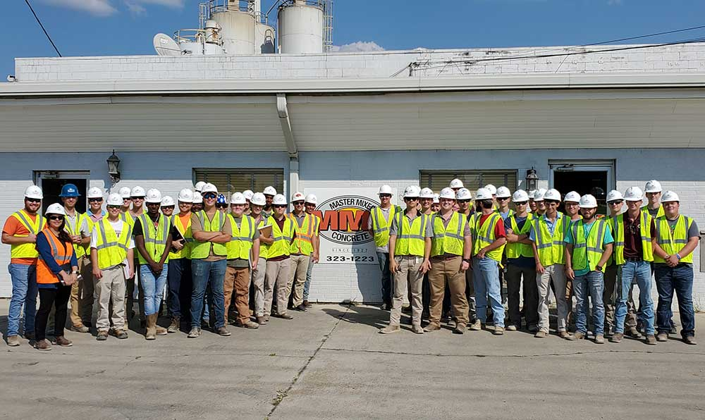 Mississippi State University School of Architecture building construction science majors in first-year studio pose in safety gear (hard hats, vests) in front of MMC building