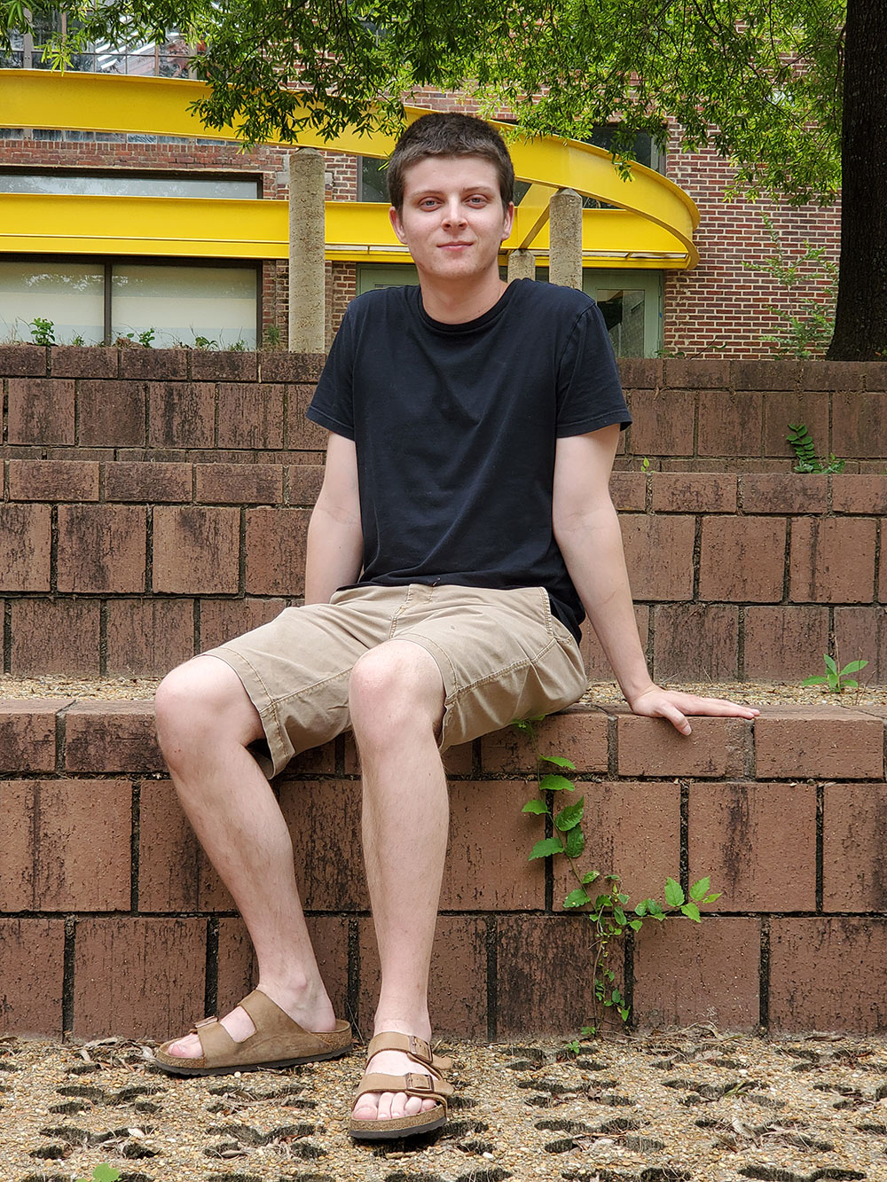 John Spraberry sits in the amphitheater area outside of Giles Hall