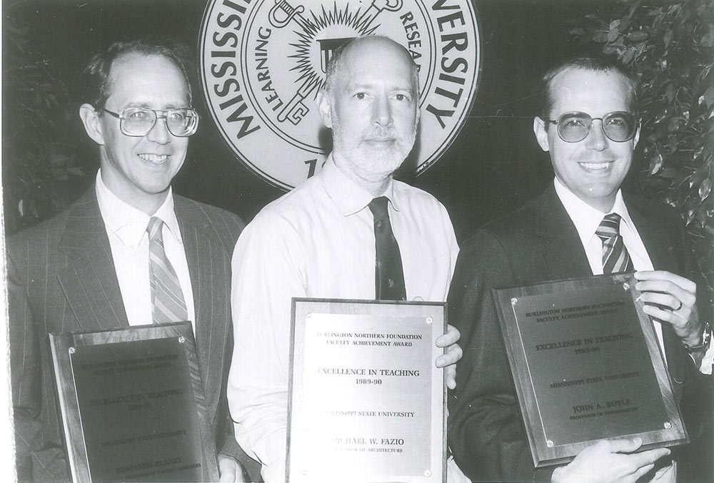 Michael Fazio, center, is shown with 2 other men holding plaques