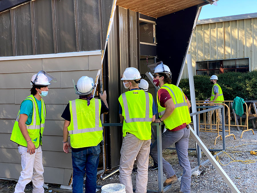 five students wearing construction PPE and masks inspect the outside of a modular building they are constructing