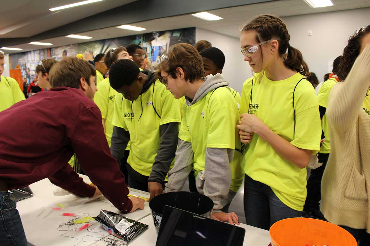 male BCS student explains their tape measure challenge to a large group of the students who attend the career fair (in yellow shirts)