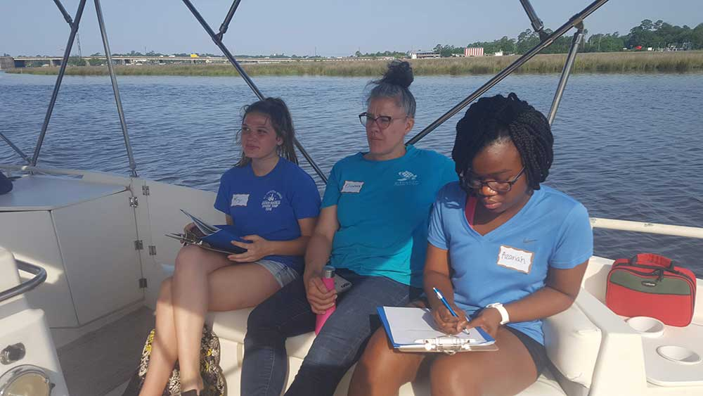 Internship boat trip and orientation. Elizabeth Englebretson (staff at GCCDS) sits in the middle of two of the student interns on a fishing boat