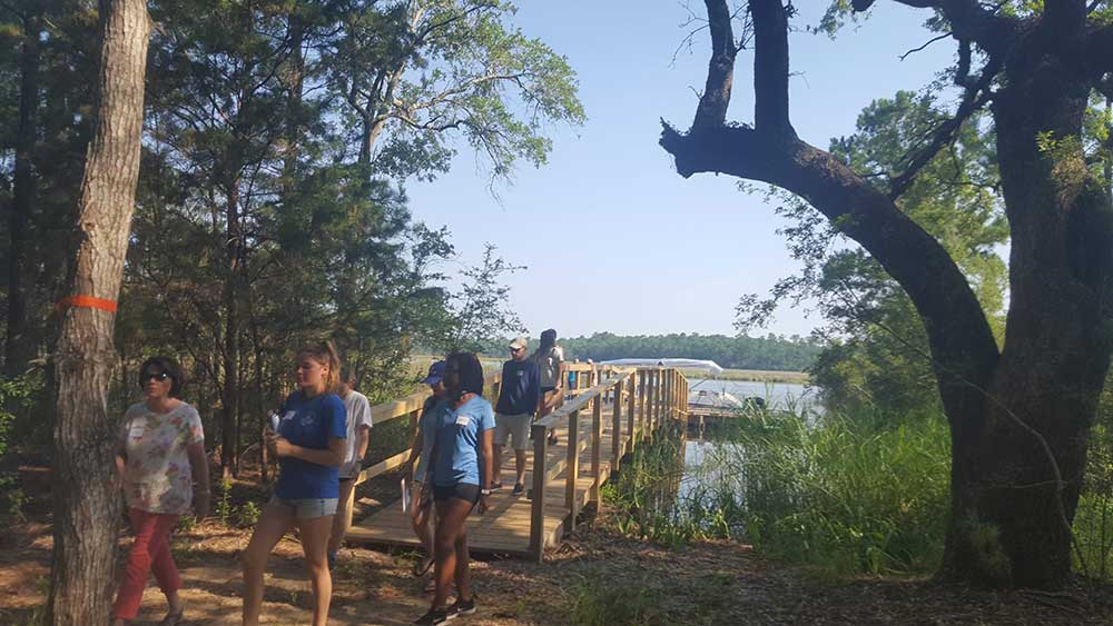 Internship boat trip and orientation. A group walks over a bridge from the water and boat into a wooded area.