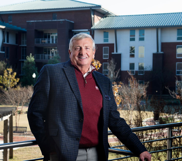 Bob Luke poses with Mississippi State University campus buildings in background