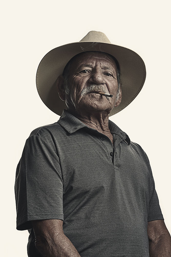 Photo by Kamau Bostic shows an older man with a cigarette in his mouth looking down at camera - wears a cowboy style hat