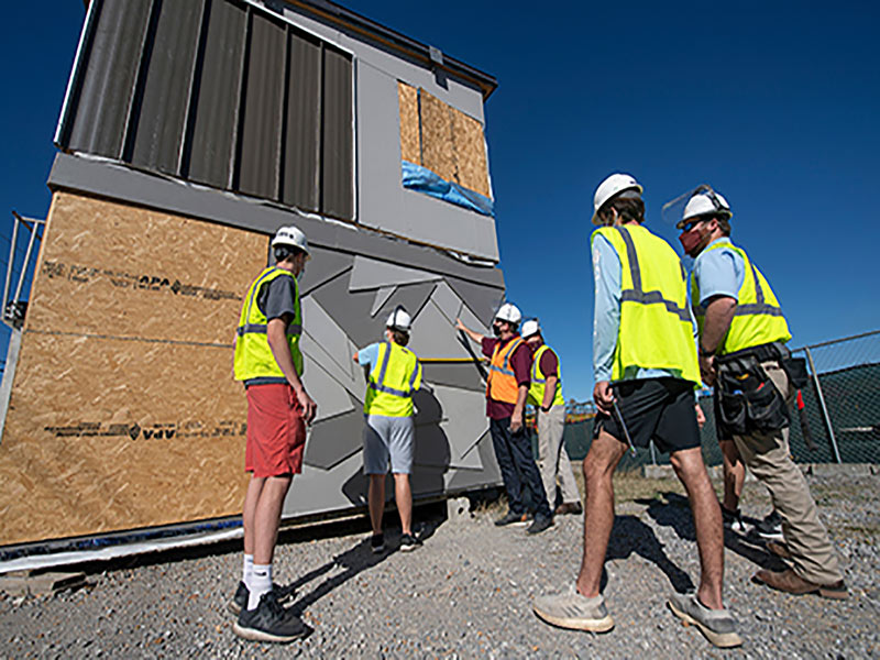 Six men in construction work gear measure and look on at a tiny, grey house they are working on.