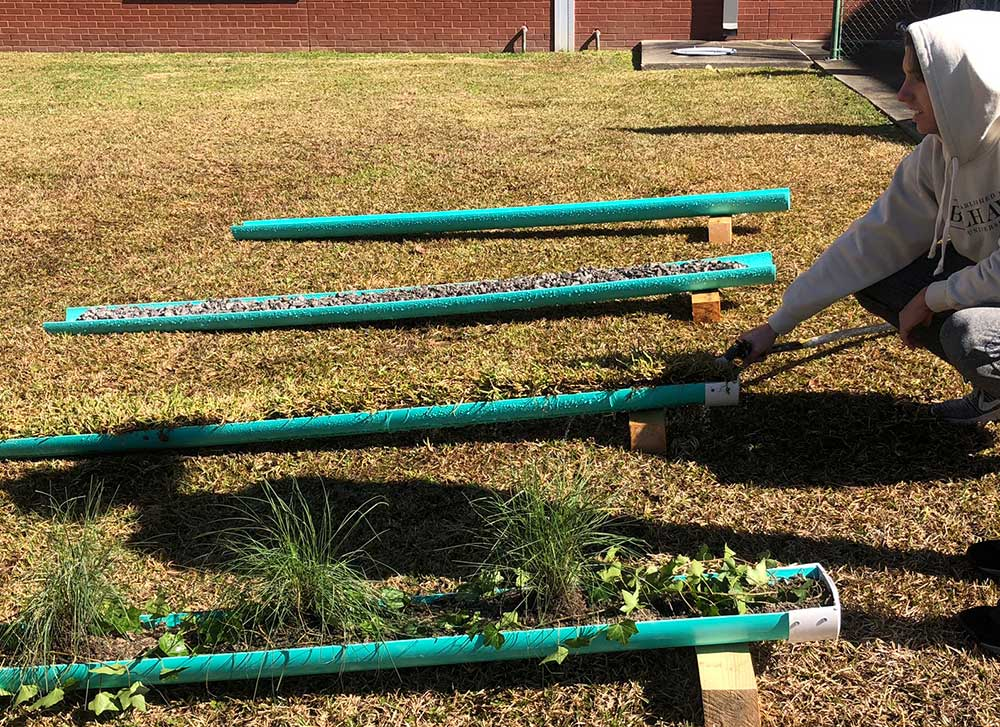 West Harrison High School student tests the varying speed of water along four 4' runnels (green pipes) shown on grass